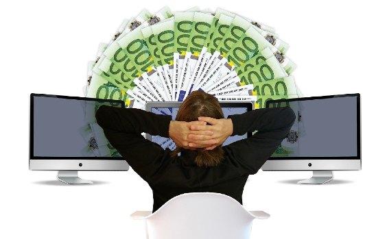 Frau vor Bildschirm mit Geldscheinen